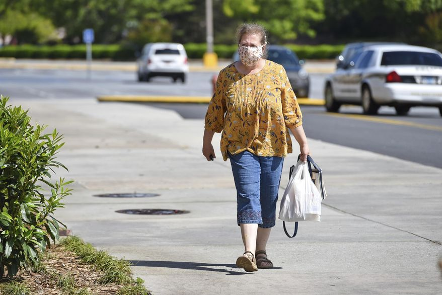 Diane McDade walks down the sidewalk after the Anderson Mall opened to limited business after South Carolina Gov. Henry McMaster eased restrictions Friday, April 24, 2020, in Anderson, S.C. (AP Photo/Richard Shiro)