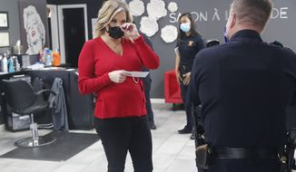 Salon owner Shelley Luther holds a citation and speaks with a Dallas police officer after she was cited for reopening her Salon A la Mode in Dallas, Friday, April 24, 2020. Hair salons have not been cleared for reopening in Texas. Luther was asked by officials to close and was issued a citation when she refused. Luther said she will remain open for business. (AP Photo/LM Otero)