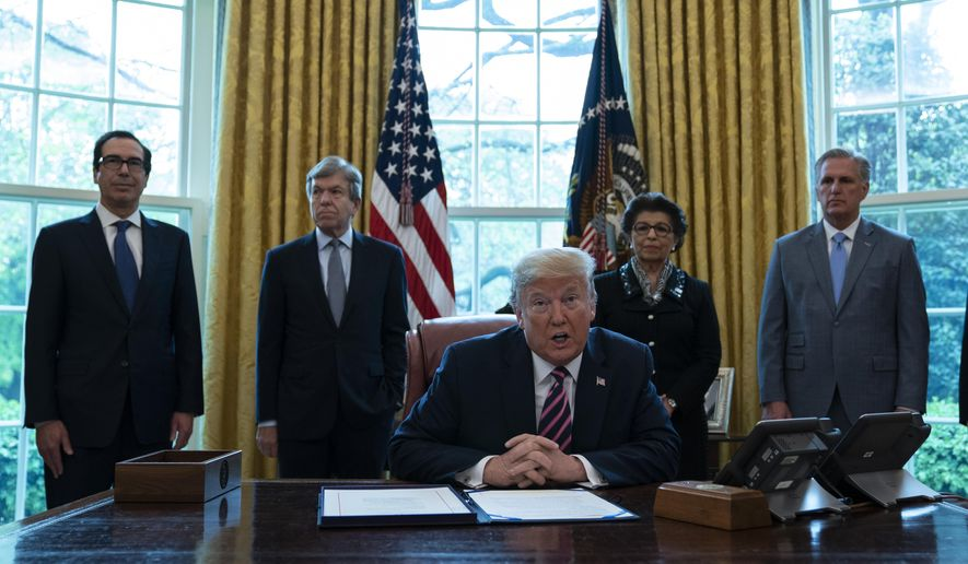 President Donald Trump speaks before signing a coronavirus aid package to direct funds to small businesses, hospitals, and testing, in the Oval Office of the White House, Friday, April 24, 2020, in Washington. From left, Treasury Secretary Steven Mnuchin, Sen. Roy Blunt, R-Mo., Trump, Small Business administrator Jovita Carranza, and House Minority Leader Kevin McCarthy of Calif. (AP Photo/Evan Vucci)