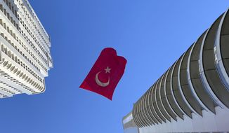 A Turkish flag suspended between two skyscrapers flutters in the wind, in Istanbul, Thursday, April 23, 2020. Turkey celebrates National Sovereignty and Children's Day on the 100th anniversary of the foundation of Turkey's parliament. Turks in the city are marking their first national holiday under lockdown amid the new coronavirus pandemic. (AP Photo/Ayse Wieting)