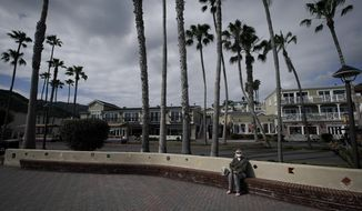 Carole Cotter, 25-year resident sits alone on the empty main shoreline street on Catalina Island in Avalon, Calif, Saturday, April 18, 2020, In the weeks that the city's normally bustling Two Harbors port has been closed due to the COVID-19 outbreak, Mayor Ann Marshall estimates the harbor alone has lost nearly $2 million in business. (AP Photo/Chris Carlson)