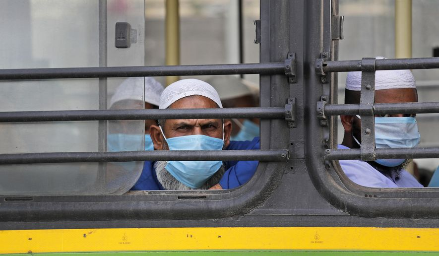 FILE - In this March 31, 2020, file photo, Muslim pilgrims wait in bus that will take them to a quarantine facility, after a government raid discovered the largest viral cluster in India at the Nizamuddin area of New Delhi, India. Muslims in India are being stigmatized after the government blamed an Islamic missionary meeting for a surge in coronavirus cases. Experts who have studied previous epidemics warn that the stigma could hamper efforts to stop the contagion and prevent many from getting themselves tested. (AP Photo/Manish Swarup, File)