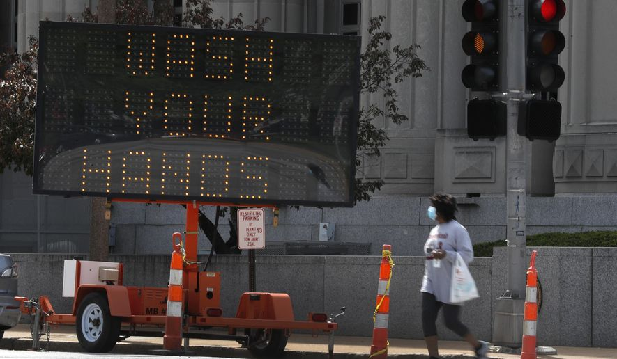 A person wears a mask while crossing a street past a sign encouraging people to wash their hands in an effort to slow the spread of coronavirus Friday, April 24, 2020, in St. Louis. (AP Photo/Jeff Roberson)