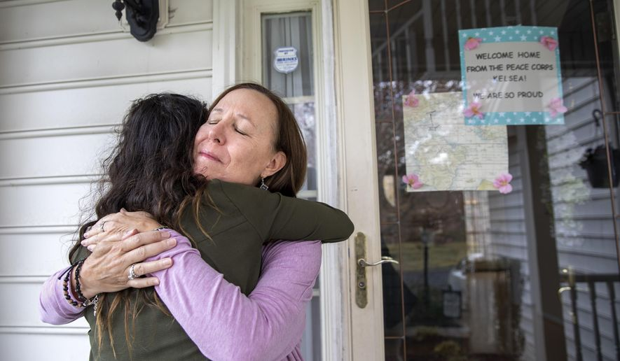 """Holly Balcom, 54, hugs her daughter Kelsea Mensh, 22, as they reunite at their home in Dumfries, Va., Wednesday, April 1, 2020, after Mensh, who had served a year in the Peace Corps in the Dominican Republic, finished her 2 week quarantine period. After evacuating her from her post, the Peace Corps put Mensh up in a hotel in her hometown to self-isolate so that she wouldn't cause any risk to her mother, who is a cancer survivor and has viral induced asthma. Though she is grateful to have been evacuated, """"I didn't get to say goodbye,"""" says Mensh, who is very worried about the community she had to leave in the Dominican Republic, """"I told my mother that in tears and we both started to cry. She said, 'I didn't get to say goodbye to the children here either.'"""" Balcom is a fourth grade teacher. (AP Photo/Jacquelyn Martin)"""