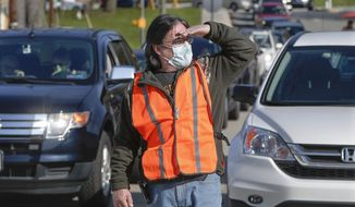 A volunteer wearing a protective mask, looks to direct the cars lined up to make purchases from their cars at the Greensburg Farmers' Market opening day, Saturday, April 25, 2020, in Greensburg, Pa. Nearly a dozen vendors sold from tents in the parking lot of the Lynch Field Park for a farmers market set up for the patrons to stay in their cars and drive from one vendor to the next to follow safety protocols during the COVID-19 pandemic.(AP Photo/Keith Srakocic)