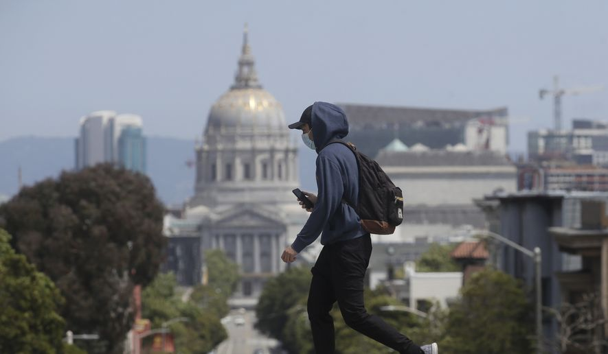 A man wears a face mask while walking in front of City Hall in San Francisco, Sunday, April 26, 2020, during the coronavirus outbreak. (AP Photo/Jeff Chiu)