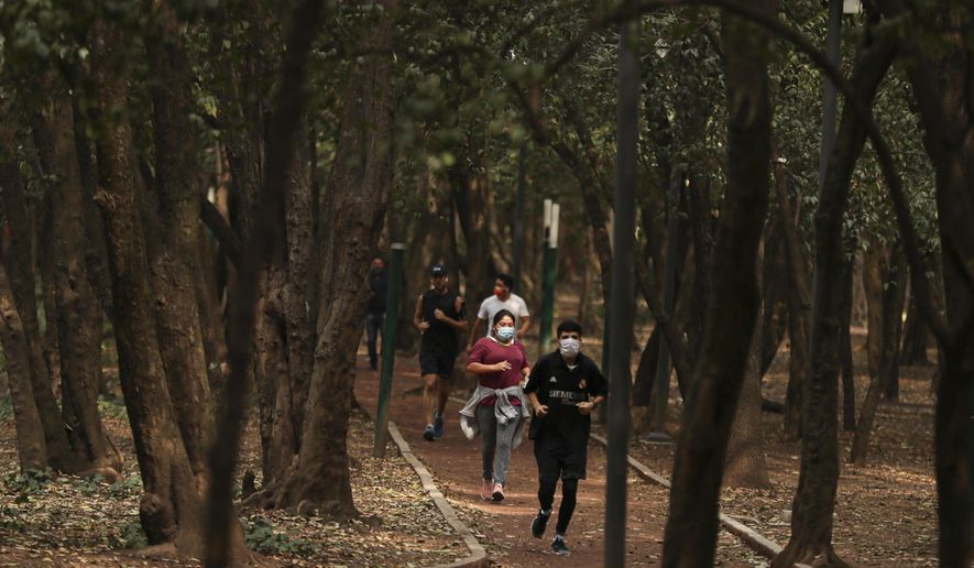 People wearing protective face mask as a precaution against the spread of the new coronavirus jog at Chalputepec park in Mexico City, Sunday, April 26, 2020. (AP Photo/Fernando Llano)