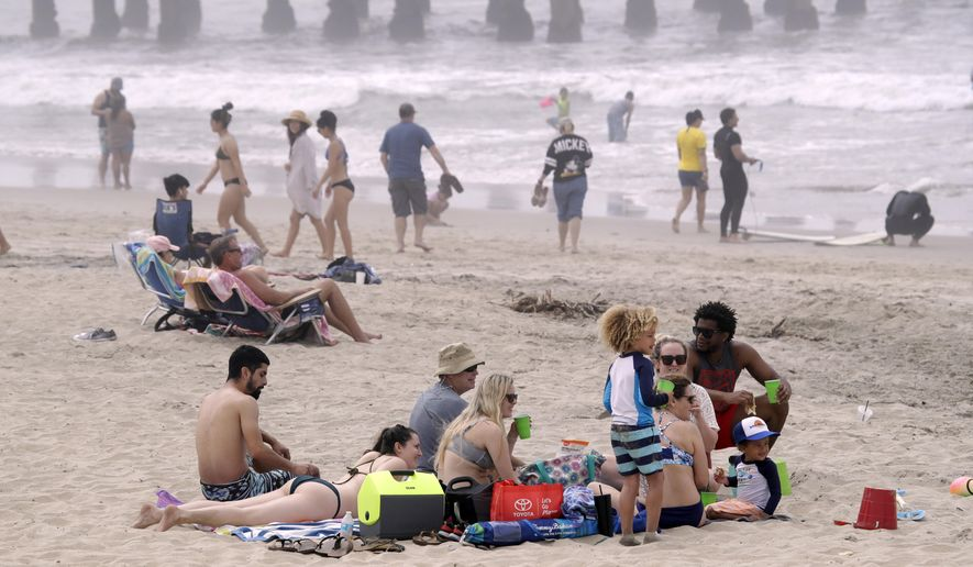 People sit on the beach Sunday, April 26, 2020, in Huntington Beach, Calif. A lingering heat wave lured people to California beaches, rivers and trails again Sunday, prompting warnings from officials that defiance of stay-at-home orders could reverse progress and bring the coronavirus surging back. (AP Photo/Marcio Jose Sanchez)