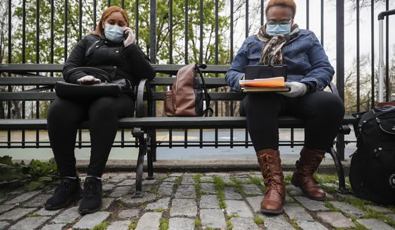 In this Thursday, April 23, 2020, file photo, Ruth Caballero, a nurse with The Visiting Nurse Service of New York, right, and Catherine Peralta, her Spanish-language translator, sit next to an empty park as they have a teleconference with a patient during their rounds in upper Manhattan in New York. Home care nurses, aides and attendants, who normally help an estimated 12 million Americans with everything from bathing to IV medications, are now taking on the difficult and potentially dangerous task of caring for coronavirus patients. (AP Photo/John Minchillo) ** FILE **