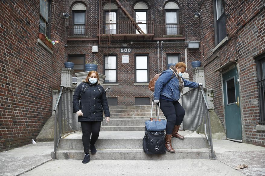 In this Thursday, April 23, 2020, photo, Ruth Caballero, a nurse with The Visiting Nurse Service of New York, right, and Catherine Peralta, her Spanish-language translator, leave a patient's home as Caballero makes her rounds in upper Manhattan in New York. Home care nurses, aides and attendants, who normally help an estimated 12 million Americans with everything from bathing to IV medications, are now taking on the difficult and potentially dangerous task of caring for coronavirus patients. (AP Photo/John Minchillo) ** FILE **