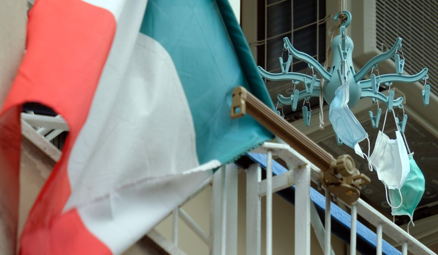 An Italian flag is hung outside a balcony along with some protective masks in Rome Thursday, April 23, 2020. The number of dead and new positives continues to plateau as Italy, the first western country to be hit by the coronavirus epidemic, in the seventh week of a nationwide lockdown following COVID-19 pandemic. (Mauro Scrobogna/LaPresse via AP)