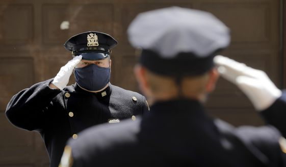 Members of the NYPD Honor Guard, wearing masks, salute as a hearse containing the remains of Traffic Section Commander Mohammed Chowdhury passes during his funeral in New York, Wednesday, April 22, 2020. Chowdhury died on Sunday, April 19, 2020, from complications related to the new coronavirus. (AP Photo/Seth Wenig)