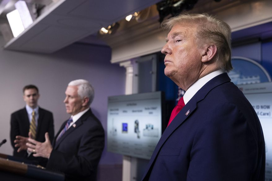 In this April 20, 2020, file photo President Donald Trump stands as Vice President Mike Pence speaks about the coronavirus in the James Brady Press Briefing Room of the White House in Washington. After two months of frantic response to the coronavirus pandemic, the White House is planning to shift President Trump's public focus to the burgeoning efforts aimed at easing the economic devastation. (AP Photo/Alex Brandon, File)
