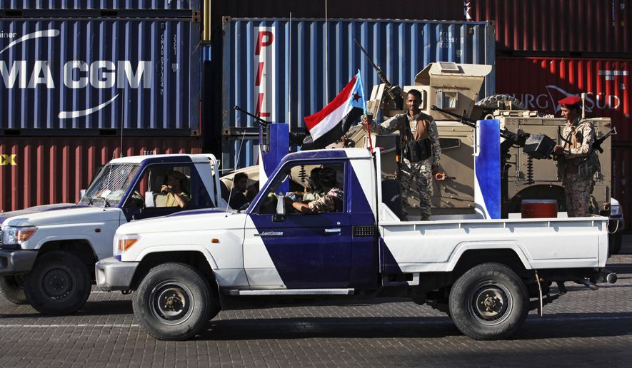 In this Wednesday, Dec. 12, 2018, file photo, soldiers allied to Yemen's internationally recognized government fly the South Yemen flag at the port of Aden in Aden, Yemen. A Saudi-led coalition mired in a yearslong war in Yemen on Monday urged Emirati-backed separatists to honor terms of a Riyadh peace deal and return control of Aden to the country's internationally recognized government. (AP Photo/Jon Gambrell, File)