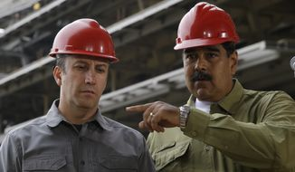 In this May 19, 2018 file photo, Venezuela's President Nicolas Maduro, right, and Vice President Tareck El Aissami tour La Rinconada baseball stadium that is under construction on the outskirts of Caracas, Venezuela. President Maduro on Monday, April 27, 2020, named El Aissami , a powerful ally sanctioned by the U.S. as a drug kingpin along with a cousin of the late socialist leader Hugo Chávez, to revamp Venezuela's oil industry amid massive gasoline shortages. (AP Photo/Ricardo Mazalan, File)
