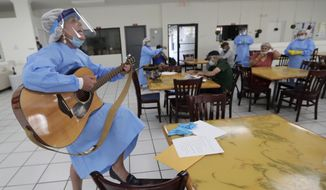Roxana Solano wears personal protective equipment as she plays the guitar and sings as residents sing along at a temporary quarantine and isolation facility for the homeless during the new coronavirus pandemic, Monday, April 27, 2020, in North Miami, Fla. This location houses people 60 and older who were living in shelters, on the street or were known to have health issues making them vulnerable to COVID-19. (AP Photo/Lynne Sladky ** FILE **)