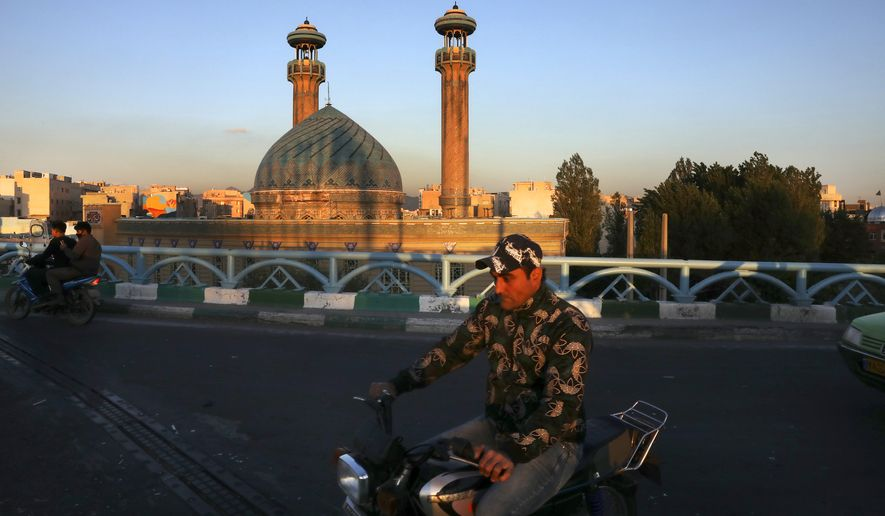 A man drives past a mosque on his motorcycle during the Muslim holy fasting month of Ramadan, in southern Tehran, Iran, Monday, April 27, 2020. In Iran, the country that is hit worst in the Middle East by the coronavirus, all religious gathering, congregational prayers and communal Iftar servings, a meal eaten at sunset to break the fast, remain forbidden in the Ramadan and also holy shrines and religious centers also continue to be closed until at least May 4. (AP Photo/Vahid Salemi)