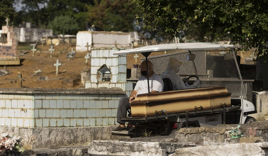 A man wearing a mask sits next the coffin of his mother as he's transported by a cemetery worker in a full protection suit to her burial site at the Nossa Senhora das Gracas cemetery in Duque de Caxias, Rio de Janeiro, Brazil, Monday, April 27, 2020. The woman's body was previously being held in a refrigerator for confirmed and suspected victims of of COVID-19, according to the administration of the cemetery. (AP Photo/Silvia Izquierdo)