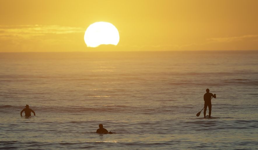 Surfers enjoy a sunrise surf at Sumner Beach as level four COVID-19 restrictions are eased in Christchurch, New Zealand, Tuesday, April 28, 2020. New Zealand eased its strict lockdown restrictions to level three at midnight to open up certain sections of the economy but social distancing rules will still apply. (AP Photo/Mark Baker)