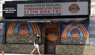 "In this April 20, 2020, photo, a pedestrian walks underneath a marquee advertising a ""Laughter is Healing"" stand-up comedy livestream event at the Laugh Factory in Los Angeles. With comedy clubs closed and concert tours put on hold, comics like Craig Robinson, Tiffany Haddish, Will C  and others are keeping the jokes flowing on webcasts and Zoom calls even without the promise of a payday, because they say the laughs are needed now more than ever. (AP Photo/Chris Pizzello)"