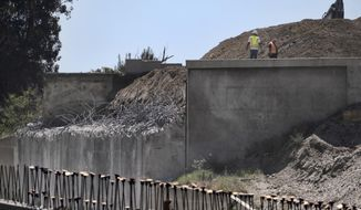 Constructions workers stand and look over an area where they had the demolition of an Interstate 5 highway bridge in Burbank, Calif., Sunday, April 26, 2020. No major backups have been reported after the major Southern California highway was closed for 36 hours in both directions while crews demolish the bridge. (AP Photo/Richard Vogel) **FILE**