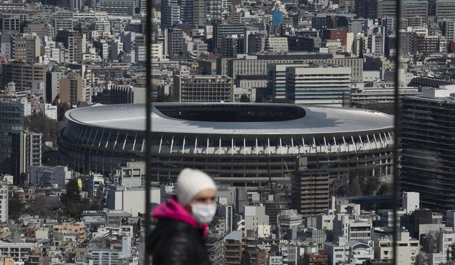 In this March 3, 2020, file photo, the New National Stadium, a venue for the opening and closing ceremonies at the Tokyo 2020 Olympics, is seen from Shibuya Sky observation deck in Tokyo. The Tokyo Olympics were postponed a month ago. But there are still more questions than answers about the new opening on July 23, 2021, and what form those games will take. (AP Photo/Jae C. Hong, File)