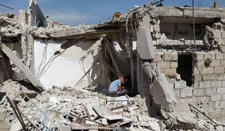 In this photo released by the Syrian official news agency SANA, boys sit amid the rubble of a house that according to the Syrian authorities was attacked by an Israeli airstrike, in the Damascus suburbs of Hajira, Syria, Monday, April 27, 2020. The Syrian military and state media said Monday that Israeli warplanes flying over Lebanon fired missiles toward areas near the Syrian capital of Damascus, killing three civilians. An opposition war monitor says four Iran-backed fighters were also killed. The military says Syrian air defenses shot some of the missiles down. The reports said the attack happened around dawn on Monday. (SANA via AP)
