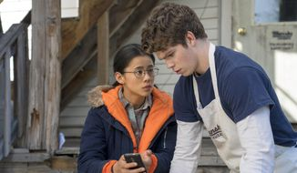 """This mage released by Netflix shows Leah Lewis, left, and Daniel Diemer in a scene from """"The Half of It,"""" a romance about a high school loner who helps a jock woo the popular girl in school. The film premieres Friday o Netflix.  (KC Bailey/Netflix via AP)"""
