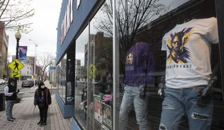 A couple of residents wearing face masks to protect from the coronavirus window shop at a closed clothing store on Main Street in downtown in Bridgeport, Conn, Monday, April 27, 2020. (AP Photo/Mary Altaffer)