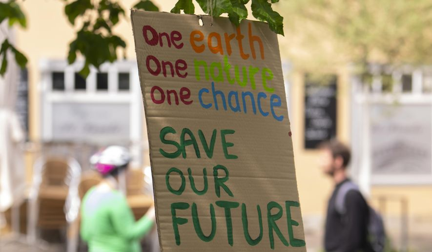 Activists of the fridays for future movement placed a poster at a tree in Erfurt, Germany, Friday, April 24, 2020. Youth groups are staging a long-planned global climate demonstration online Friday because of restrictions on public protests during the coronavirus pandemic. Giant slogan reads 'Fight Every Crises'. (AP Photo/Jens Meyer)
