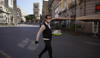 Bartender Antonio is on his way to deliver coffee in Naples, Monday, April 27, 2020. Region Campania allowed cafes and pizzerias to reopen for delivery Monday, as Italy it is starting to ease its lockdown after a long precautionary closure due to the coronavirus outbreak. (AP Photo/Andrew Medichini)
