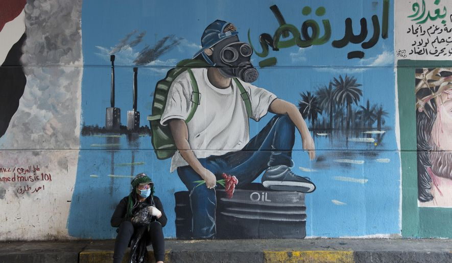 "FILE - In this Dec. 8, 2019 file photo, a protester rests by a mural with Arabic that reads, ""I want my oil,"" in Baghdad, Iraq. The historic crash in oil prices in the wake of the novel coronavirus pandemic is reverberating across the Middle East as crude-dependent countries scramble to offset losses from a key source of state revenue. Iraq faces the most dire situation, and officials are trying to find ways to cut spending. Iraq saw massive protests the past months by a populace angry over the weak economy and rampant corruption -- and the turmoil could erupt again. (AP Photo/Nasser Nasser, File)"