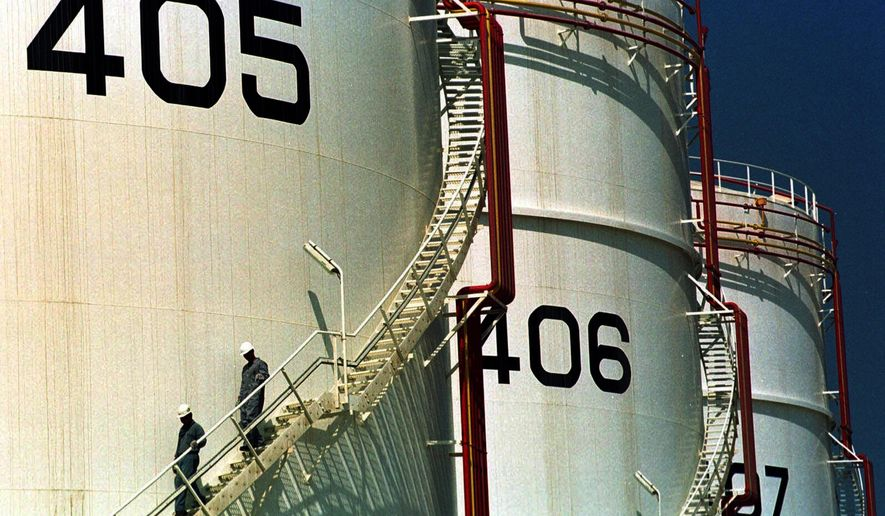 In this Sept. 25, 2000, file photo, two workers climb down from one of the tanks in an oil tank-farm in Jebel Ali, 25 miles (40 km) south of Dubai in the United Arab Emirates. The historic crash in oil prices in the wake of the novel coronavirus pandemic is reverberating across the Middle East as crude-dependent countries scramble to offset losses from a key source of state revenue. The economies of all the Arab Gulf oil exporters are expected to contract this year. (AP Photo/Kamran Jebreili, File)
