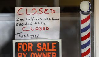 "FILE - In this April 2, 2020 file photo, ""For Sale By Owner"" and ""Closed Due to Virus"" signs are displayed in the window of a store in Grosse Pointe Woods, Mich. The second round of loan applications for the government's small business relief program has been slowed by computer issues at the Small Business Administration. Lenders complained Monday, April 27, that they couldn't get their applications into the SBA system known as ETran that processes and approves loans. (AP Photo/Paul Sancya, File)"