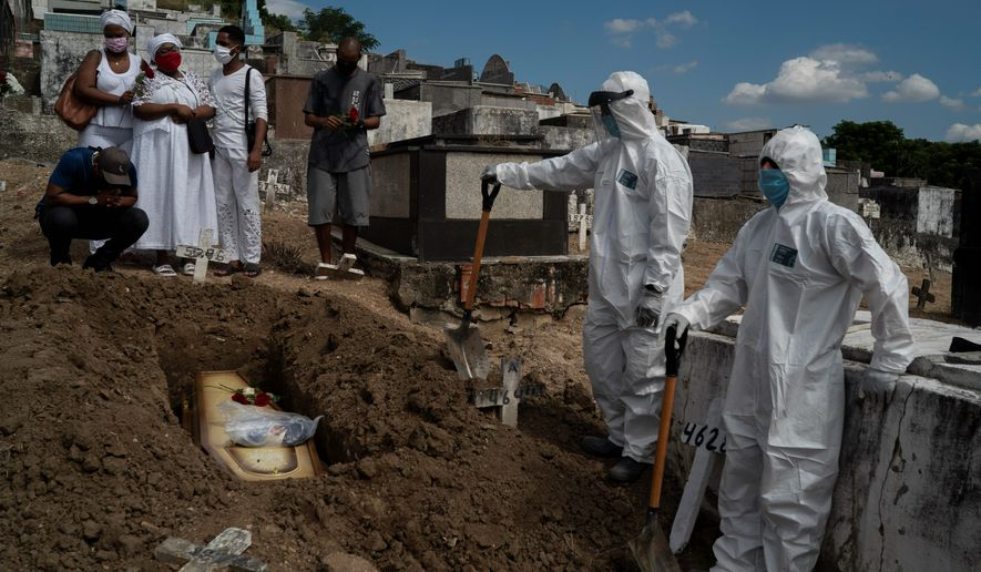 Taina dos Santos (third from left) attends the burial of her mother Ana Maria, who died from the coronavirus, in Rio de Janeiro on Tuesday. Experts fear Brazil may be the next global hot spot for the coronavirus with death totals reaching 4,600. (ASSOCIATED PRESS)