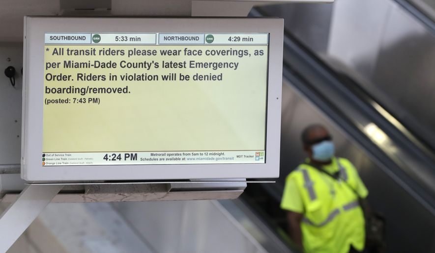 A man goes down an escalator near a monitor advising passengers to wear face coverings, Tuesday, April 28, 2020, in downtown Miami. The Transport Workers Union of America filed a lawsuit against Miami-Dade County Transportation & Public Works Director Alice Bravo on April 17, citing the lack of safety and protection of workers and passengers from the new coronavirus. (AP Photo/Wilfredo Lee)