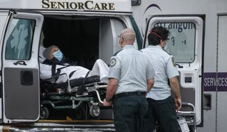 A patient is loaded into the back of an ambulance by medical personnel amid the coronavirus pandemic, Tuesday, April 28, 2020, outside NYU Langone Medical Center in New York. (AP Photo/John Minchillo)
