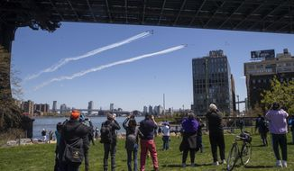 Spectators watch from the Brooklyn bridge park as a formation of U.S. Navy Blue Angels and U.S. Air Force Thunderbirds fly over the East River, Tuesday, April 28, 2020, in New York. The flyover was in salute to first responders in the fight against the new coronavirus. (AP Photo/Mary Altaffer)