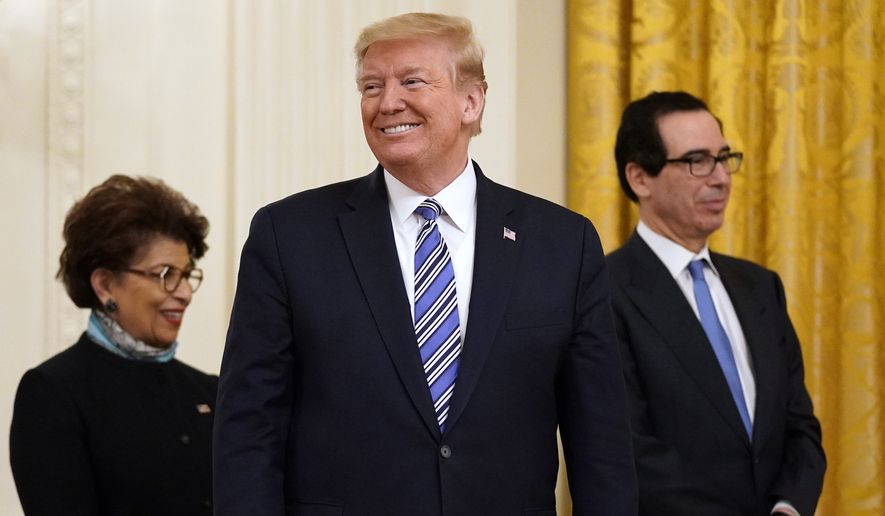 President Donald Trump smiles during an event about the Paycheck Protection Program used to support small businesses during the coronavirus outbreak, in the East Room of the White House, April 28, 2020, in Washington. At left is Jovita Carranza, administrator of the Small Business Administration and Treasury Secretary Steven Mnuchin, watching. (AP Photo/Evan Vucci)