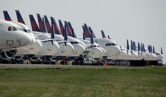FILE - In this April 1, 2020, file photo, several dozen mothballed Delta Air Lines jets are parked at Kansas City International Airport in Kansas City, Mo.  Investors are now getting their first look at companies navigating the coronavirus pandemic. A clearer snapshot of the business landscape should start to formulate by keeping an eye on the busiest week of the earnings season as many companies are reporting earnings on Tuesday, April 28. (AP Photo/Charlie Riedel, File)