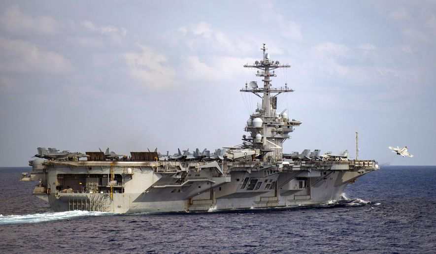 In this March 18, 2020, photo provided by the U.S. Navy, an F/A-18F Super Hornet launches from the flight deck of the aircraft carrier USS Theodore Roosevelt (CVN 71) in the western North Pacific Ocean. The crew of the USS Theodore Roosevelt remains sidelined in Guam with a coronavirus outbreak but is inching toward getting healthy and returning to sea duty. At the same time the fate of the aircraft carrier's former captain remains unresolved, although the Navy's top officer has recommended reinstatement of Capt. Brett Crozier. (Mass Communication Specialist 3rd Class Nicholas V. Huynh/U.S. Navy via AP))