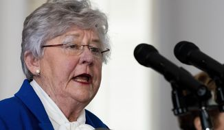 Governor Kay Ivey announces continued social distancing during her coronavirus update Tuesday, April 28, 2020 at the state capitol building in Montgomery, Ala. In the background is State Health Officer Dr. Scott Harris. (Mickey Welsh/The Montgomery Advertiser via AP)