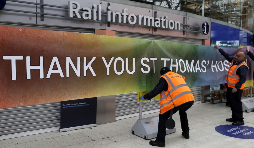 Staff at Waterloo Station in London put up a banner to thank nearby St Thomas' Hospital, Tuesday, April 28, 2020. The highly contagious COVID-19 coronavirus has impacted on nations around the globe, many imposing self isolation and exercising social distancing when people move from their homes. (AP Photo/Kirsty Wigglesworth)