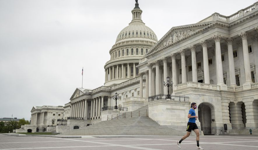 A man wearing a mask depicting American flags jogs past the U.S. Capitol Building, Tuesday, April 28, 2020, in Washington. The U.S. House of Representatives has canceled plans to return next week, a reversal after announcing it a day earlier. (AP Photo/Andrew Harnik)