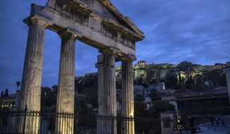 People walk in front of the Gate of the ancient Roman agora with the ancient Acropolis hill seen in the background in the traditional Plaka district of Athens, as lockdown measures continue to prevent the spread of the coronavirus, on Monday April 27, 2020. (AP Photo/Petros Giannakouris)