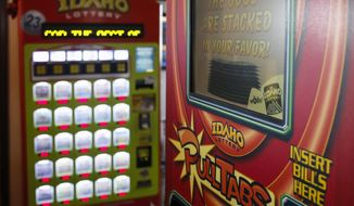 FILE - This file photo taken March 5, 2015, shows an Idaho Lottery scratch ticket vending machine, left, and an Idaho Lottery PullTabs machine at Westy's Garden Lanes in Garden City, Idaho. Despite a pandemic, many Idahoans are feeling lucky. Idaho Lottery Director Jeff Anderson said Tuesday, April 28, 2020, that ticket sales are down but not that much since Idaho went under a stay-at-home order on March 25 due to the coronavirus. He says the largest prize since the order is one for $250,000 this week from an Ultimate Diamond Jackpot game in south-central Idaho. He says buying a lottery ticket can bring a sense of normalcy. (AP Photo/Otto Kitsinger, File)