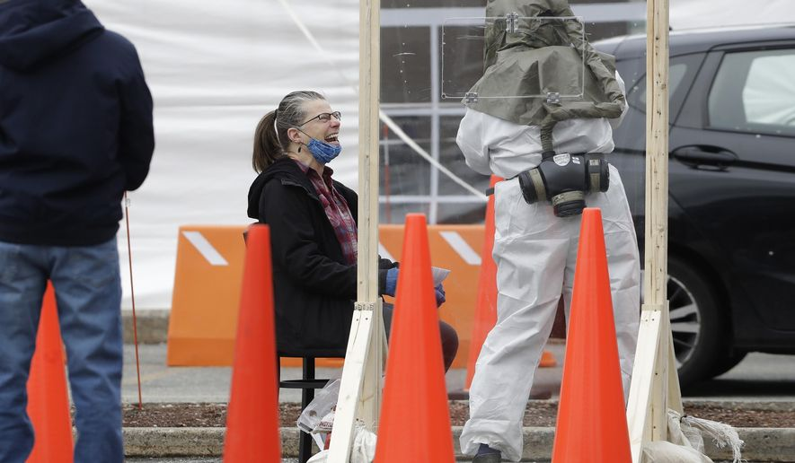 Gail Harkins, of Somerville, Mass., center left, reacts after being administered a COVID-19 test by a medical worker in protective equipment, right, Tuesday, April 28, 2020, at a testing site in a parking lot of a hospital, in Somerville. (AP Photo/Steven Senne)
