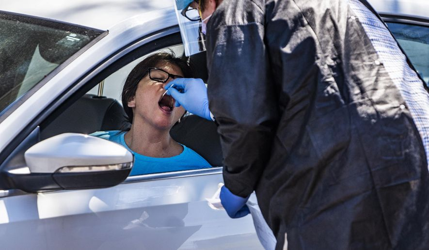 Alma Lopez gets tested for the coronavirus in a drive-thru setting at the People's Center Clinics & Services in Minneapolis on Monday, April 27, 2020. (Richard Tsong-Taatarii/Star Tribune via AP)