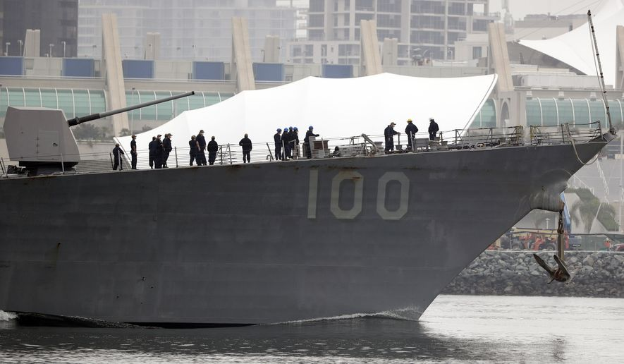 Crew members look on as the USS Kidd passes downtown San Diego as it returns to Naval Base San Diego, Tuesday, April 28, 2020, as seen from Coronado, Calif. As the American destroyer heads home with an outbreak in cases of COVID-19, relatives and friends of the 350 crew members prayed for their health while Navy officials vowed to keep the outbreak, the second to strike a Navy vessel at sea, from spreading. (AP Photo/Gregory Bull)