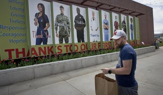 A man walks out of a restaurant with a take away bag in front of a mural expressing appreciation for first responders, in Omaha, Neb., Tuesday, April 28, 2020. Gov. Pete Ricketts defended his decision Monday to ease social-distancing restrictions in some parts of Nebraska, even though the number of confirmed coronavirus cases has surged in the last few days. (AP Photo/Nati Harnik)